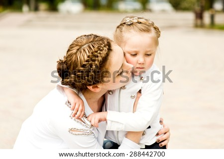 Beautiful and lovely girl hugging her mother in a park a sunny summer day. - stock photo