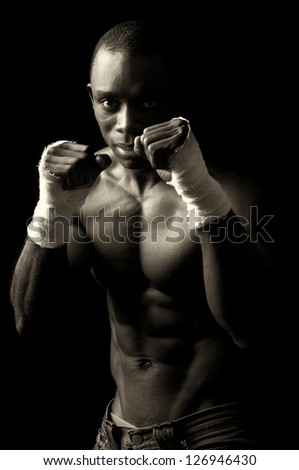 Beautiful and muscular black man in dark background - stock photo
