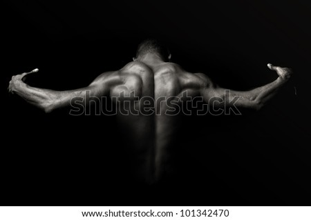 Beautiful and muscular black man's back in dark background - stock photo