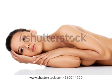 Beautiful and naked woman laying on the floor with her hands under head. Isolated on white.  - stock photo