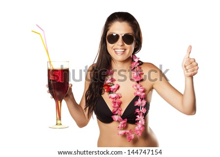 beautiful and nice brunette with a flower necklace and sunglasses holding her cocktail and showing thumbs up