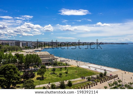 Beautiful and picturesque bird's eye view to the promenade of Thessaloniki,Greece.Landscape of blue cloudy sky, green park and sea captured from the landmark building of this city - the White Tower. - stock photo