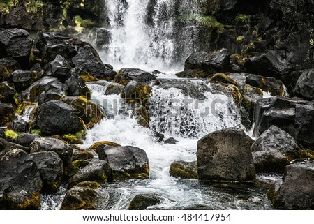 Beautiful and powerful icelandic waterfall with moss rocks in foreground in summer.