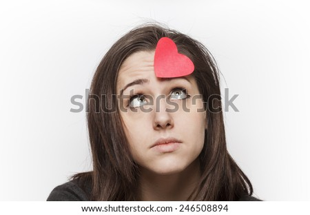 Beautiful and sad girl looking at a paper heart on her forehead - stock photo