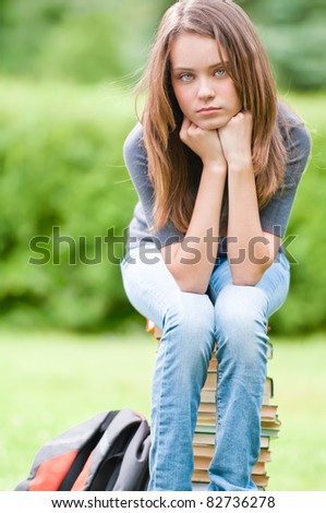 beautiful and sad young student girl sitting on pile of books, looking into the camera. Summer or spring green park in background - stock photo