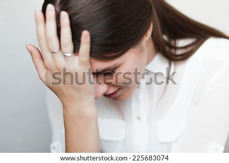 Beautiful and sad young woman. Headache or problems, hand at her forehead.  - stock photo