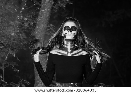 Beautiful and scary devil. Devil woman in halloween concept. Halloween make up sugar skull beautiful model.