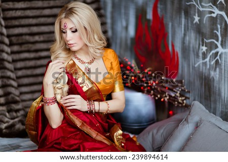 Beautiful and sensual blonde girl in Indian red saree on the background of red lights and looks away