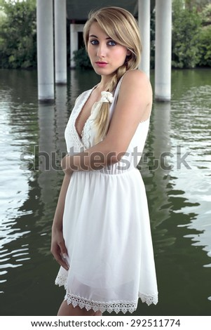 beautiful and sensual girl with long blond hair posing on the shore of a river / Portrait of elegant woman blonde under bridge - stock photo