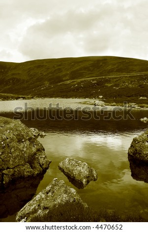 Beautiful and serene Highland Lochan high up in Glen Clova in Perthshire in Scotland in duotone