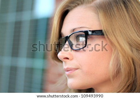 Beautiful and Serious Business Woman Wearing Eye Glasses Looking To The Side - stock photo