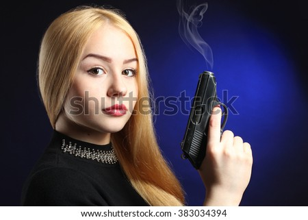 beautiful and serious girl with pistol on dark blue background - stock photo