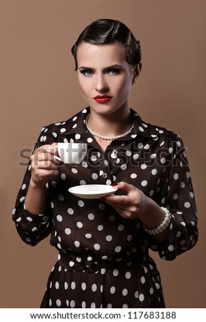 Beautiful and serious vintage woman with cup of coffee - stock photo