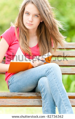 beautiful and serious young student girl sitting on bench, holding book in her hands and looking into the camera. Summer or spring green park in background - stock photo