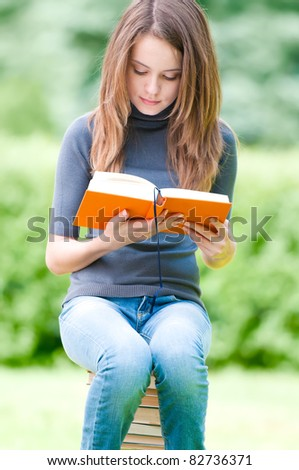 beautiful and serious young student girl sitting on pile of books, holding book in her hands and reading. Summer or spring green park in background - stock photo