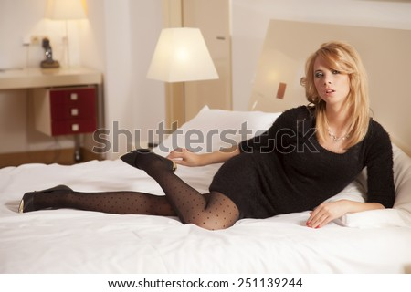 Beautiful and sexy attractive sensuality pretty young adult blonde woman wearing elegance fashionable black dress lying on the bed in bedroom luxury style hotel apartment