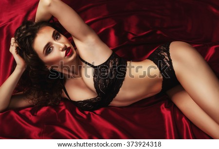 Beautiful and sexy glamour woman seduces over red silk in black lace lingerie
