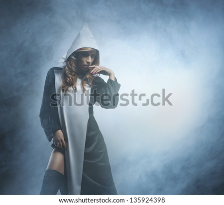 Beautiful and sexy nun over the smoky background - stock photo
