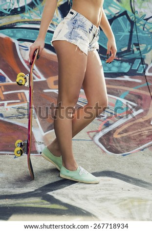 Beautiful and sexy street girl with her skateboard - stock photo