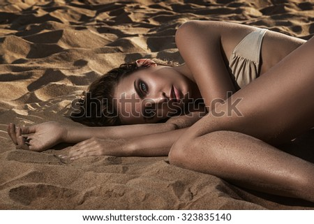 Beautiful and sexy woman lying on the sand
