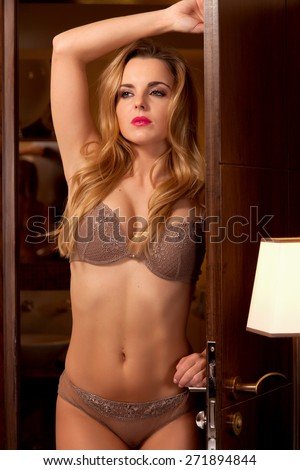 Beautiful and sexy young adult sensuality attractive pretty blonde babe woman in brown lingerie in the door of a luxury style hotel apartment - stock photo