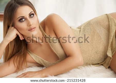 Beautiful and sexy young adult sensuality brunette woman in gold blouse on the window on luxury apartment - stock photo