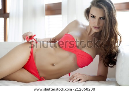 Beautiful and sexy young adult sensuality brunette woman in red bikini on the white sofa in luxury apartment - stock photo