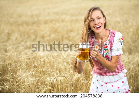 Beautiful and sexy young blond woman drinking beer in wheat field background. soft daylight - stock photo