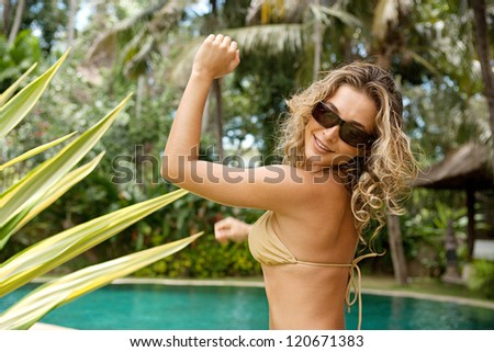 Beautiful and sexy young woman dancing in a golden bikini near a swimming pool in a topical garden during a sunny day on vacations.