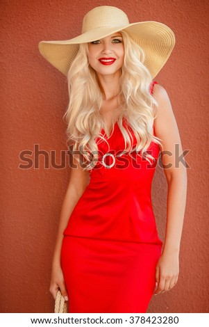 beautiful and sexy young woman in red dress, red lips and straw hat. Summer portrait of a beautiful young blonde Caucasian girl with straight hair in blue dress outdoors in the city.Fashion Woman - stock photo