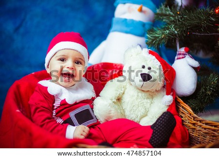 beautiful and smiling baby dressed as Santa Claus