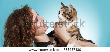 Beautiful and smiling girl holding cat letterbox - stock photo