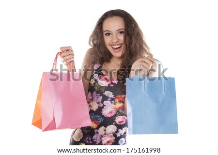 beautiful and smiling teenage girl holding shopping bags on white background