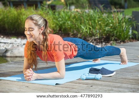 Beautiful and sporty woman doing plank outdoors