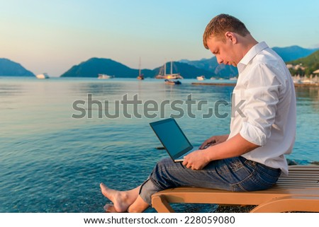 beautiful and very successful male working outdoors - stock photo