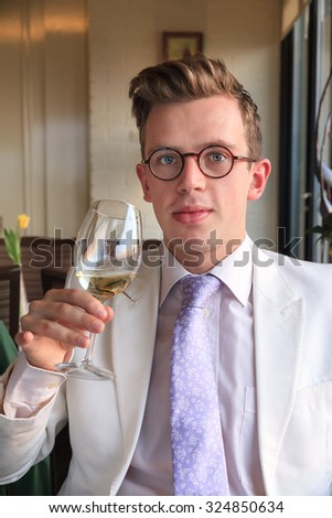 Beautiful and well dressed young man enjoying the tasting of a white wine in the afternoon in the Netherlands