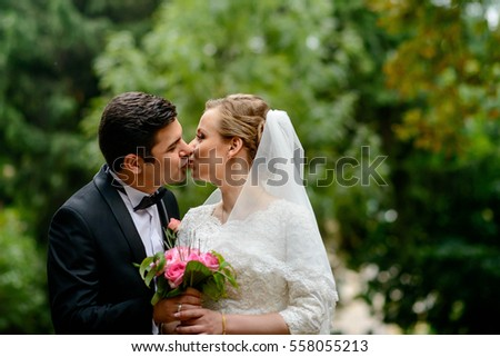 beautiful and young bride and groom kiss each other outdoors