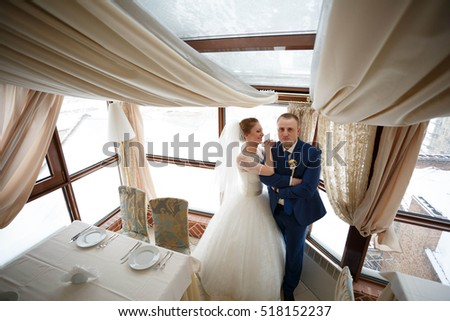 beautiful and young bride and groom standing in a restaurant