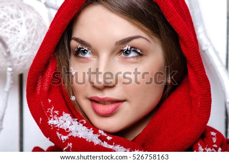 Beautiful and young caucasian model in red scarf over her face. On her face is false snowflakes.