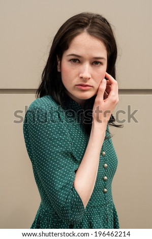 Beautiful and young female model touching her natural face. The background is a metal wall. - stock photo