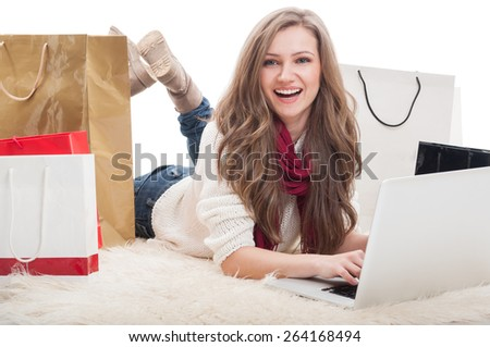 Beautiful and young female shopper using laptop. Online shopaholic concept. - stock photo