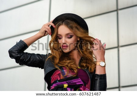 Beautiful and young girl in a hat walking in the city