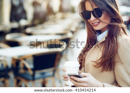 Beautiful and young girl in sunglasses writes a message on a cell phone and drinking coffee outdoors - stock photo