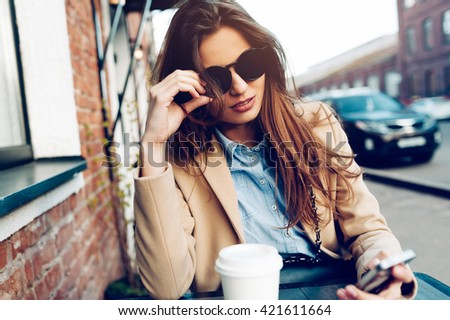 Beautiful and young girl resting in a summer cafe. Woman drinking coffee and writing a message on her phone - stock photo