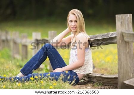 Beautiful and young girl wearing casual outfit posing sitting on the fence with a smile - stock photo