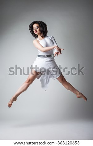 beautiful and young gymnast on a gray background during speech