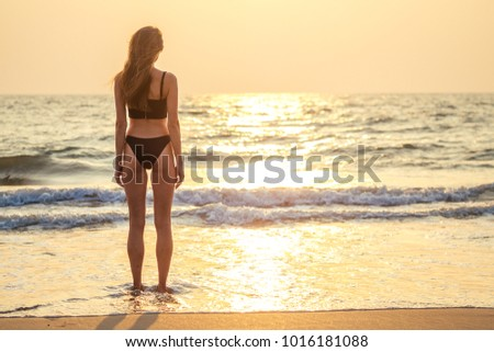 beautiful and young woman looks at the sunset beach
