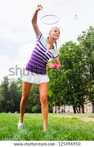 beautiful and young woman playing badminton - stock photo