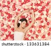 beautiful and young woman with background full of roses - stock photo