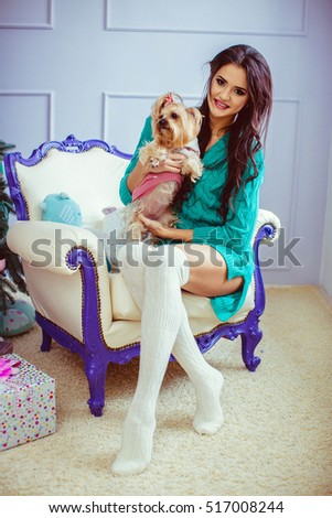 beautiful and young woman with her cute dog sitting on white chair